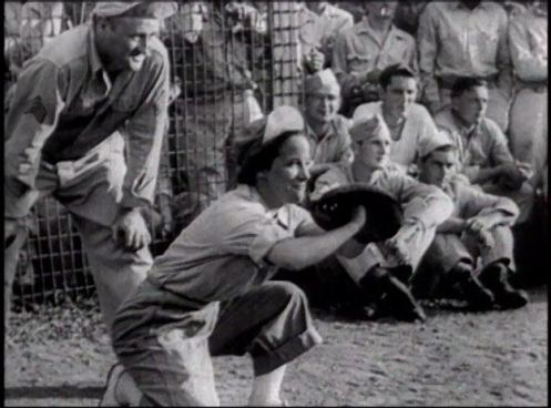 A woman in uniform acts as catcher in a ballgame while sodiers watch.