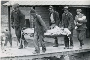 People carry a patient on a cot out of a house, a nurse with an infant follows.