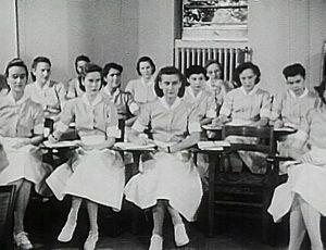 Women in white nursing uniforms sit in a classroom.