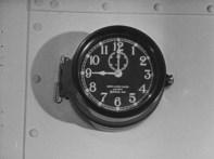 A clock on the bulkhead reads nine o'clock.