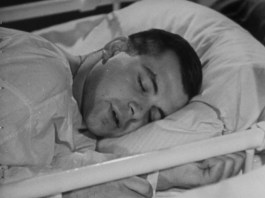 A patient sleeps in a hospital bed.