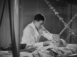 A sailor cleans a patient lying in a hanging cot.
