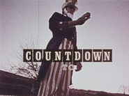 "Man dress in blue, white, and red holding something round, with the title ""Countdown to..."""