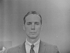 a man in a suit staring into the camera with a thinking face.