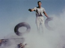 A man tosses tires onto a fire.