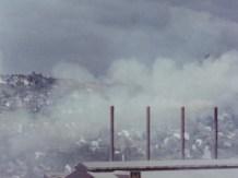 Smoke masks a hillside town.