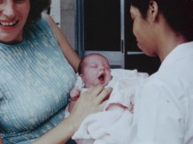 A newborn yawns in the arms of a woman.
