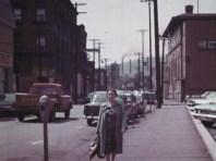 Woman on the sidewalk posing in front of street