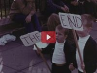 Children walk with signs that read The End.