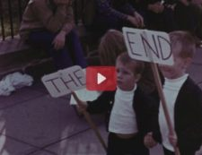 Boys march with signs that read The End