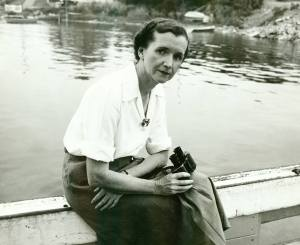 A woman in a skirt an blouse sits on a railing over water holding binoculars.