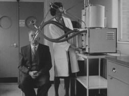 woman using a machine on a man that has his mouth on a stick connected to tube connected to the box like machine.