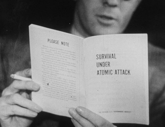 Film still: a man smoking a cigarette reads a pamphlet titled Survival Under Atomic Attack.