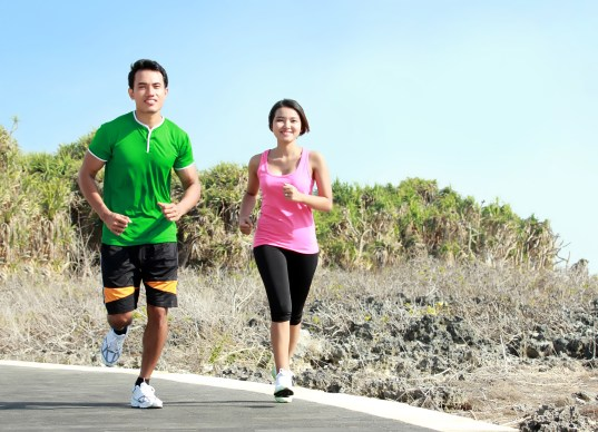 young couple running together on jogging track