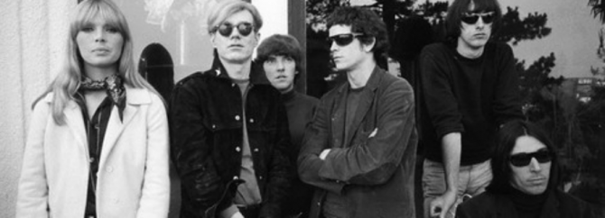 black-and-white photo of Nico and Andy Warhol standing next to Lou Reed and other Velvet Underground members