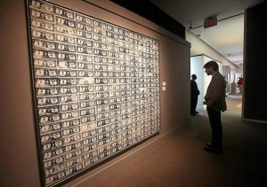 Andy Warhol's 200 One Dollar Bills on a gallery wall with a visitor viewing the painting