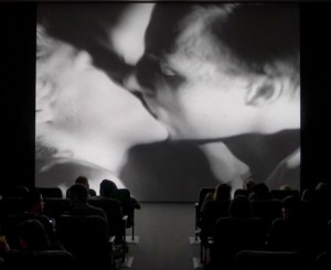 black and white photograph of an audience in a theater watching Andy Warhol's Kiss