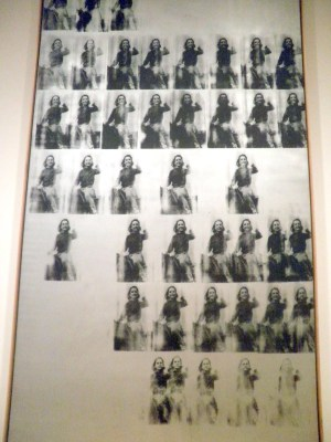 photograph of Andy Warhol's canvas National Velvet featuring a screen printed young Elizabeth Taylor riding a horse and printed  dozens of times across and down the canvas.
