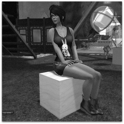 Neeva Torok sitting on the 1st BAOC Trophy, a plywood cube, in Fanny Vermont's studio