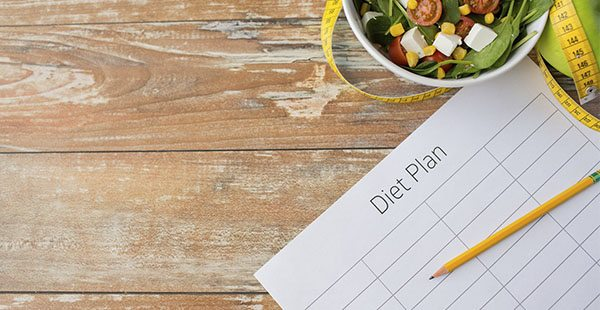 46993167 - healthy eating, dieting, slimming and weigh loss concept - close up of diet plan paper green apple, measuring tape and salad