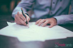 Homem escrevendo em papel branco com caneta.