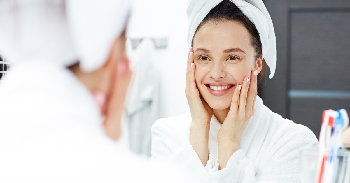 Woman looking in the mirror smiling. MEDIjobs