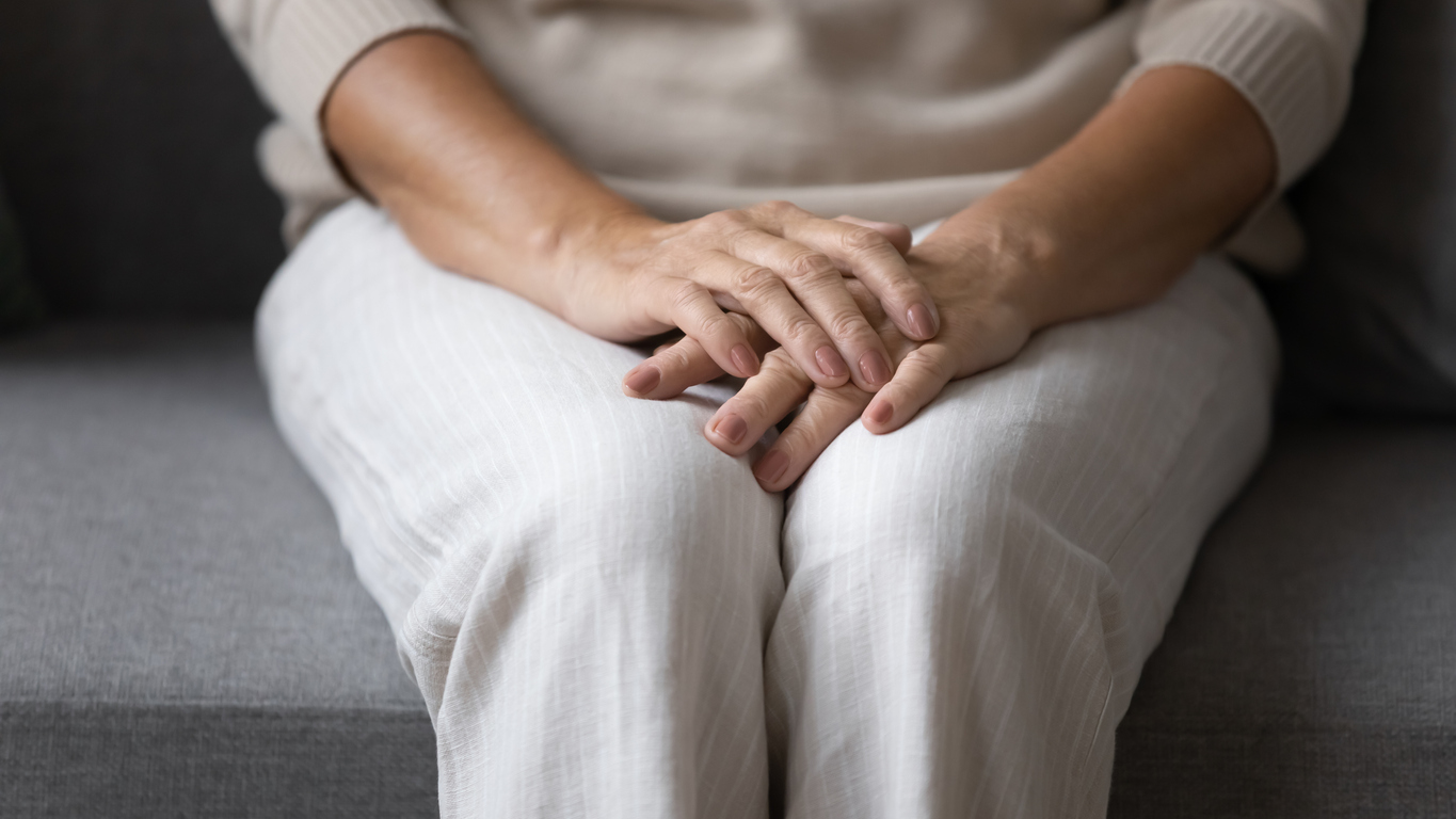 Close up elderly senior woman sitting on sofa, holding folded hands on lap, feeling lonely at home. Middle aged mature lady suffering from depression, recollecting memories alone in living room