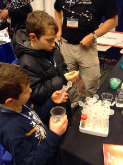 """Noah Oxer, 11, and brother Josh Oxer, 8, participate in a wheat germ experiment at a booth by the University of Wisconsin's Biotechnology Center. """"They enjoy science,"""" says their mother Kelly Oxer. """"It's right up their alley."""""""