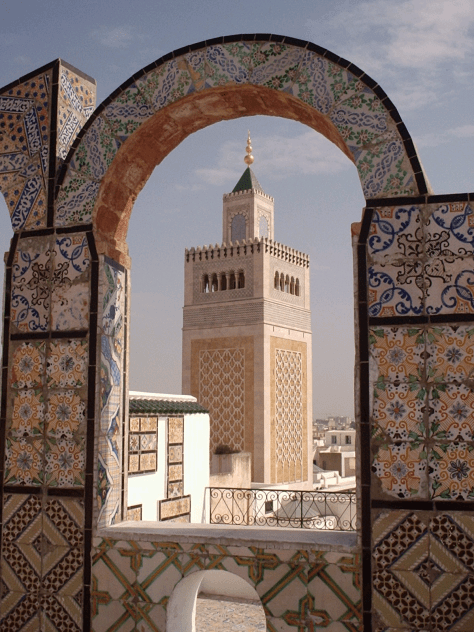 The minaret of the Zaytuna Mosque Image in Tunis, Tunisia, seen from the roof of a neighbouring commercial building.