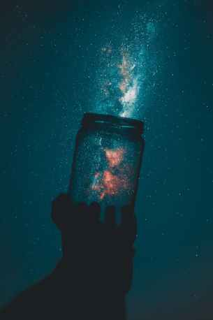 silhouette of person holding glass mason jar