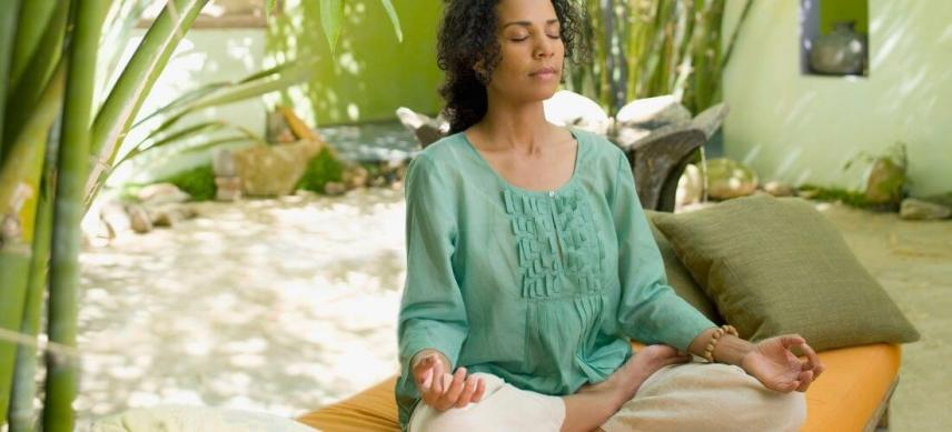 woman meditating in her outdoor meditation space