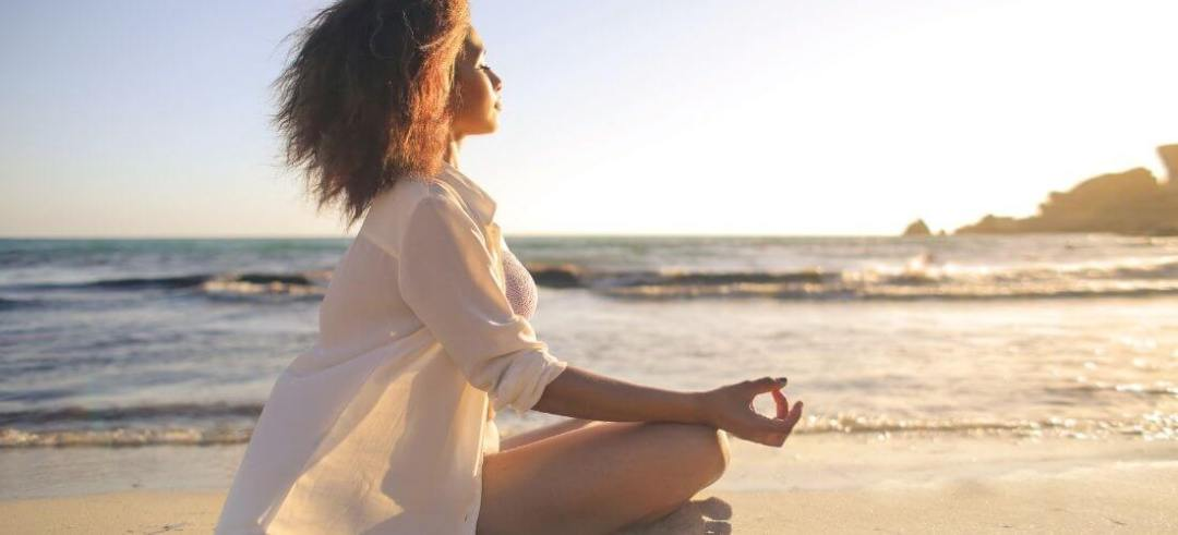 how to escape the age of ignorance woman meditaing at the beach
