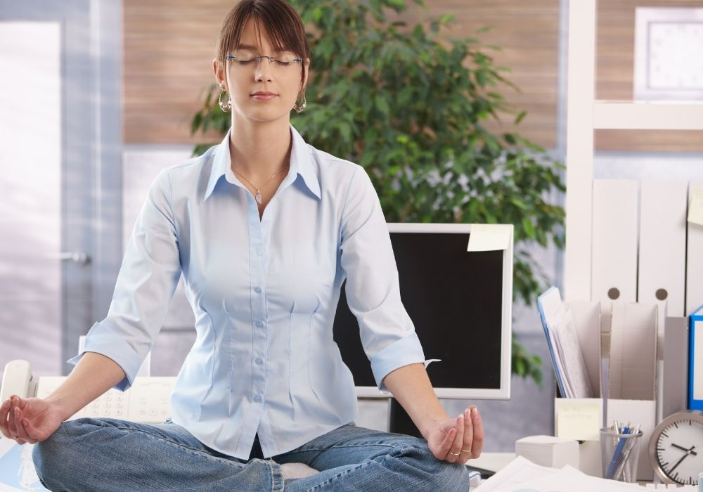 how to meditate for beginners woman meditating on top of desk