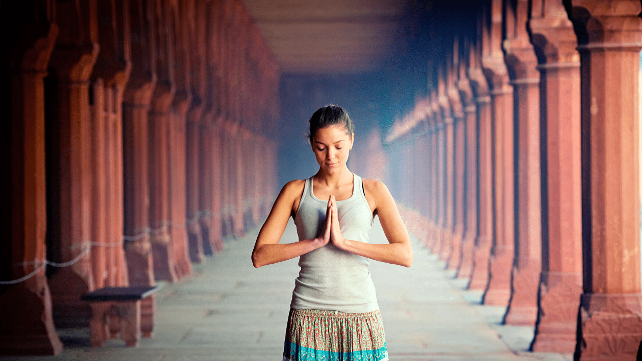 girl standing with hands praying signifying Om Shri Anantaha Mantra