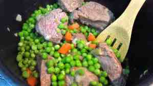 Add green peas to meat, carrots and onions.