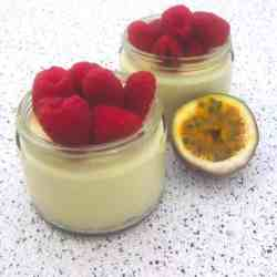 Two jars with passion fruit mousse topped with raspberries shown next to an actual passion fruit cut in half.