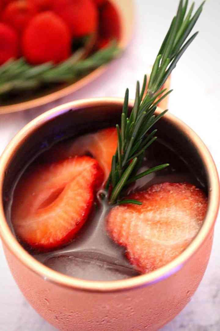 Perfect Holiday Cocktail: Açai Strawberry Moscow Mule Caipiroska!!  The cocktail is decorated with a rosemary twig.