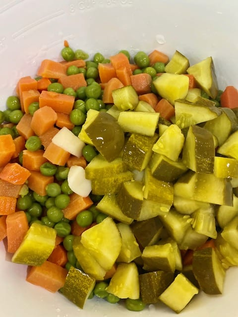 Add diced dill pickles to salad bowl