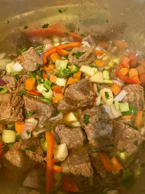 Adding beef and stock to the sauteed vegetables