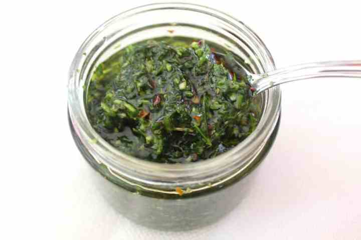 A jar of chimichurri sauce with a spoon ready to serve.