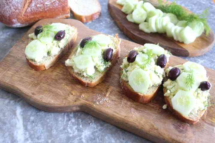 Toasted slices of bread with olive oil are then topped with feta cheese, olives, cucumber and dill.