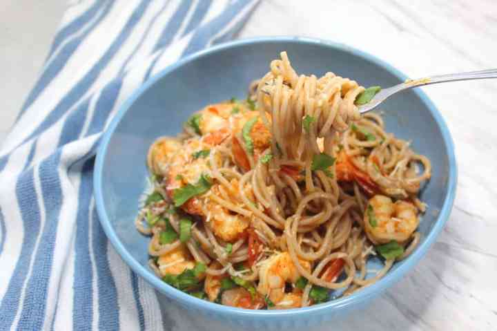Pasta bowl full of gluten free pasta tossed with shrimp tomato pasta sauce and garnished with cilantro.