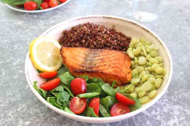 Healthy Salmon, Red Quinoa Dinner plate filled with fresh spinach, grape tomatoes and lima beans.