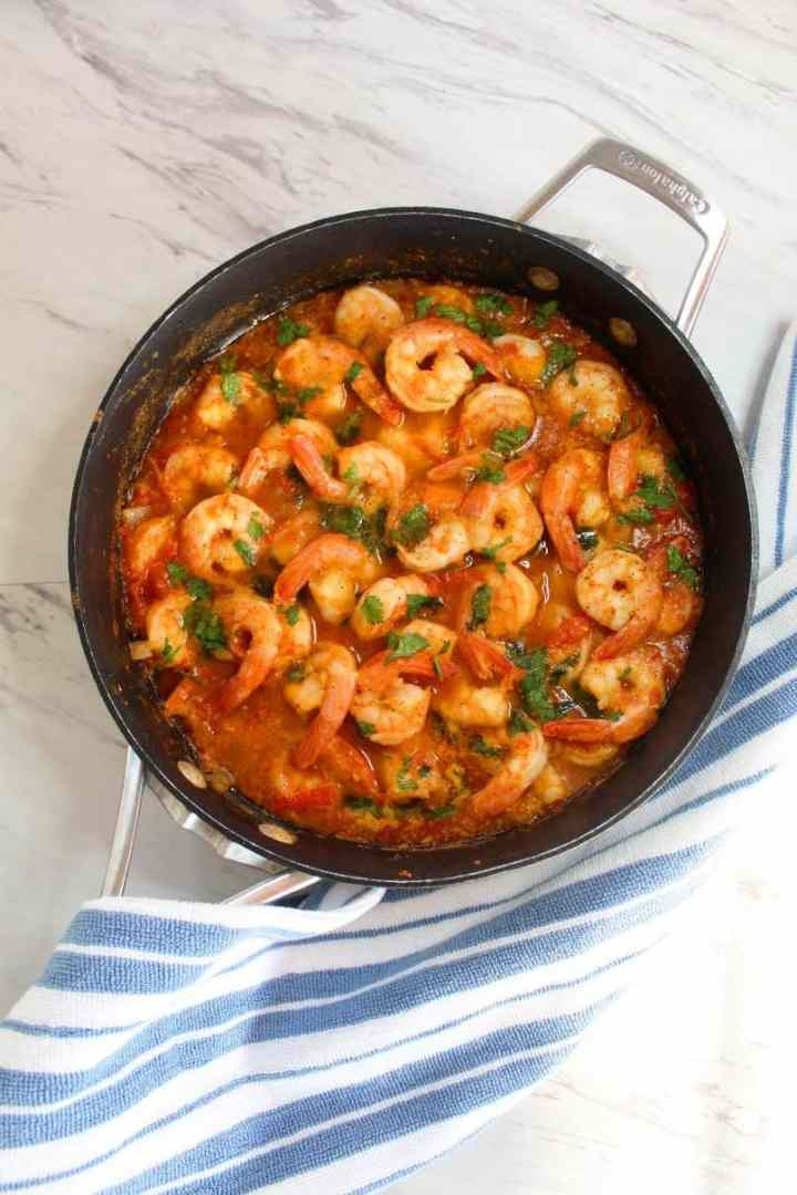 Shrimp tomato pasta sauce in a skillet. Sauce is garnished with cilantro.