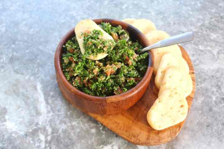 A bowl of tabouli salad served with mini pita breads.