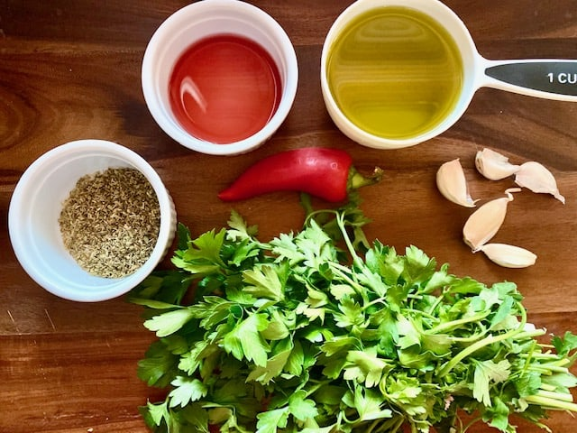 Ingredients to make homemade chimichurri in a cutting board: parsley, oregano, red wine vinegar, olive oil, red chili pepper and garlic.