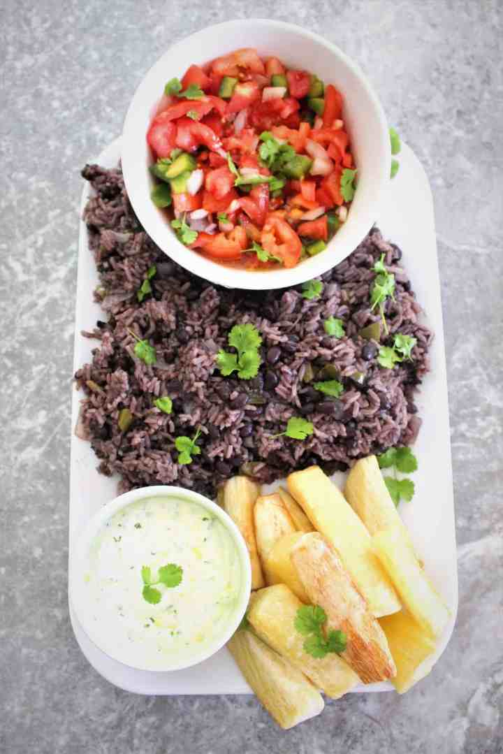 Family style dinner, rice and black beans, fried yucca, dip and pico de gallo all served in a platter.