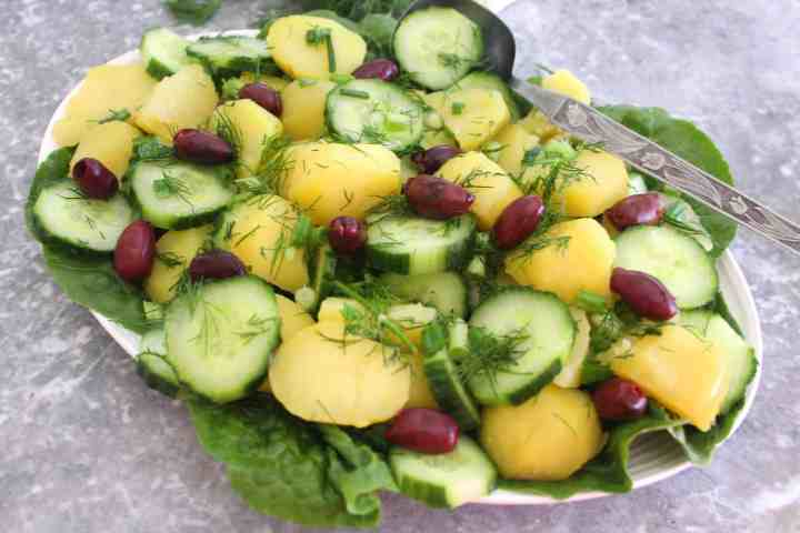 No mayonnaise potato salad shown on a platter ready to be served. Salad is over a bed of lettuce, topped with cucumbers, dill, kalamata olives.