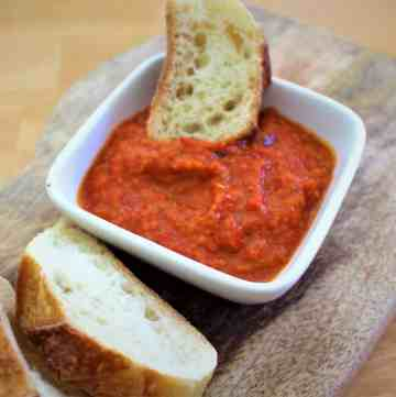 Red pepper dip shown in a white recipient with bread dipping in it.