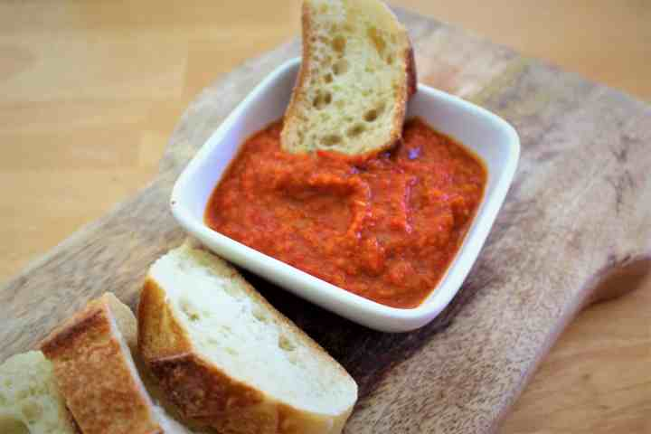 Ajvar sauce used as dip, picture shows a slice of bread dipped in the sauce.